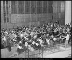 Photograph of choir and orchestra practicing on stage in the Joseph Smith Memorial Building