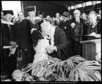 [President David O. McKay kisses a small girl who had given him a lei at commencement exercises,...