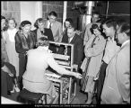 [President Wilkinson and others watch the use of a weaving loom, ca. 1952]