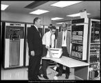 [C. Edwin Dean and Gary Carlson supervise a technician installing new computer equipment in the...