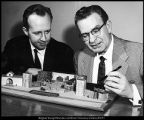 "[Crawford Gates and Harold I. Hansen use a model stage to plan a production of ""Sand in their..."