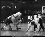 [President Ernest Wilkinson does push-ups at a basketball game while Cosmo encourages him, March...