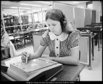 "[A student uses the new ""sound page"" system installed in the library for studying..."