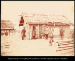 [Men and boy, standing in front of a hut]