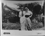 Two women in front yard of house